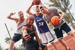 Going crazy together. Group of young men in sports clothing taking selfie and smiling while standing outdoors Royalty Free Stock Image