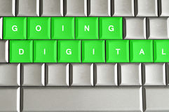 Going digital spelled on a metallic keyboard. Going Digital spelled on a silver metallic keyboard Stock Images