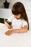 Going doing school work. Young caucasian girl doing her homework while sitting at table Royalty Free Stock Photography