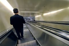 Going down 01. Solitary man going down using an escalator (retouched Stock Photo