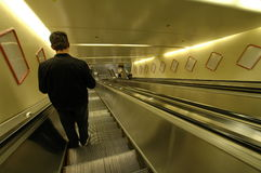 Going down 02. Solitary man going down using an escalator (original Royalty Free Stock Photos