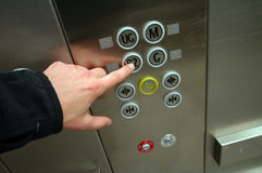 Going down. Man hand pushing B2 button in chrome elevator Stock Photos