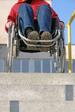 Going down. Wheelchair woman trying to go down the concrete stairs stock photo
