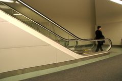 Going down. One person going down an escalator Stock Photography