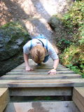 Going Down. Woman descending wood ladder Stock Photo