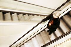 Going down. Female going down with the escalator in a department store - motion blur Royalty Free Stock Image