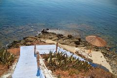 Blue stairs to rocky beach with umbrellas and relaxing chairs. Going down blue stairs to rocky beach with umbrellas and relaxing chairs Stock Photos