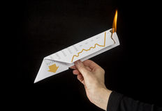 Going Down in Financial Flames. Concept photo showing a hand launching a paper airplane which is on fire and pointed down to illustrate the financial markets Royalty Free Stock Images