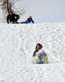 Children Having Fun in the Snow. Sliding Down a Hi Royalty Free Stock Photo