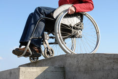 Going down the kerb. Closeup of wheelchair woman going down the concrete kerb royalty free stock photo