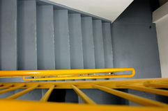 Going Down Stairs. Looking striaght down a flight of stairs with a bright yellow handrail Royalty Free Stock Photo