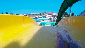 Going down the water slide in aqua park stock footage