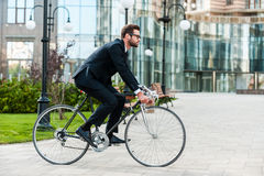 Going everywhere by his bike. Side view of young businessman looking forward while riding on his bicycle Royalty Free Stock Photos