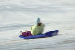 Going fast. A girl heads down the hill in the snow on her sled Royalty Free Stock Image