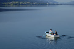 Going fishing. Father and son set off in their rowing boat, out on to the lake one calm sumer's morning Stock Photography