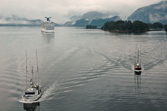Going, Going, Gone Fishing!. Two fishing boats in Sitka, Alaska with cruise ship in the background Royalty Free Stock Image