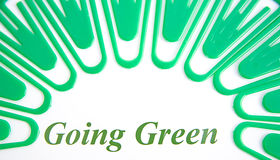 Going green. Eight identical green plastic paper clips arranged in a semi circle around the words ' going green '. The image, on a plain background, is stock photos