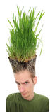 Going Green. A young man looking upward at the grass growing from the roots on top of his head. This concept can apply to environmentalists, farmers, agriculture Royalty Free Stock Photo