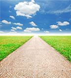 Going Green for the Future. Alone way green grass coundy blue sky to destination and green way to the future royalty free stock photos