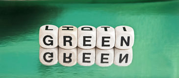 Going green. Text ' green ' spelled out in upper case black letters on small white cubes  on green background Stock Photos