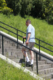 Going Higher. Man walking up stairs outside surrounded by landscape on a sunny summer day royalty free stock photography