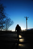 Going Home. A person is silhouetted in a backlit sunset (could be sunrise) image, walking along a dark road.  The scene (trees, telephone pole, power lines, road Royalty Free Stock Photo