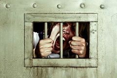 Going Insane. Cross-processed image of a man going insane, grabbing the bars of his jail cell, looking rabid and screaming uncontrollably Stock Images