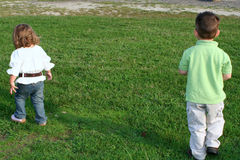 Going My Own Way. Young brother and sister walking away in opposite directions stock images