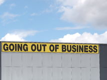 Going out of business writing in black on yellow letters on a white cladded industrial building. Going out of business writing in black on yellow letters on a Royalty Free Stock Images
