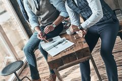 Going over details. Close up top view of two men choosing design while spending time in the workshop royalty free stock images