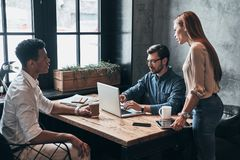 Going over details. Group of young confident business people dis Stock Photo