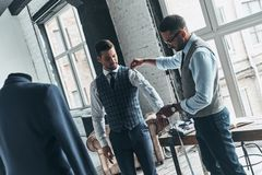 Going over details. Young fashionable designer measuring client?s sleeve while standing in his workshop stock photos