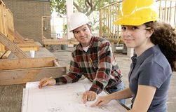 Going Over the Job. A construction foreman going over the blueprints with a female apprentice royalty free stock image