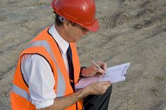 Going over plans. Image depicting a professional studying plans at a greenfield building site Royalty Free Stock Photos
