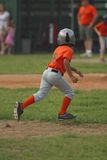 Going for Second. Little league player running for second base with his eye on the ball in play Royalty Free Stock Photo