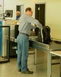 Going through security. A business man prepares to go through security at an airport Stock Photos