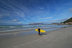 Going surfing. Surfer going surfing at Muizenberg Beachfront in Cape Town Stock Images