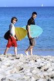Going surfing. Two boys walking alongbeach with surf boards Stock Images