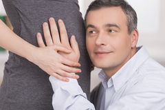 He is going to be a father. Happy mature man leaning to his pregnant wife belly and smiling Stock Images