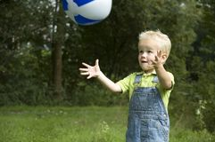 Going to catch it. Little boy is going to catch the ball stock images