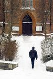 Going to church in winter. A man going towards old catholic gothic church in winter Royalty Free Stock Photo