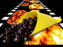 Going to the cinema. Chocolate raisin in paper bag lying on the film reel Royalty Free Stock Images