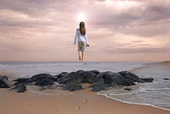 Going to Heaven. Young girl seemingly walking off the beach toward the light to be with God in heaven Royalty Free Stock Image