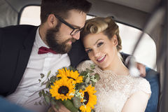 Going to a honeymoon. Young newlywed couple sitting in a retro vintage car, hugging and going away on a honeymoon Stock Photography