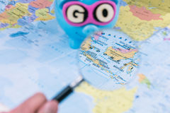 Going to Indonesia. Magnifying picked travel spot on the map. Saving piggy bank with sunglasses and GO slogan staying on. The world map in background stock image