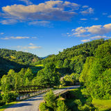Going to nature throug the bridge. Asphalt road going through the bridge off into mountains on the left, passes through the green shaded forest Royalty Free Stock Photos
