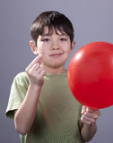 Going to pop a balloon. A young boy with a smirk on his face gets ready to pop a ballooon stock photography