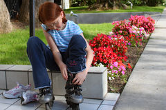 Going to roll. Girl putting on roller-blades Stock Image