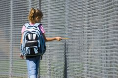 Going to School. Little girl walking to school by school fence on beautiful sunny day wth back pack and pencil Royalty Free Stock Photography