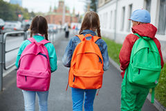 Going to school. Backs of schoolkids with colorful rucksacks moving in the street Royalty Free Stock Image
